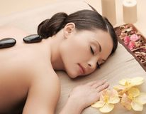Asian woman in spa with hot stones Royalty Free Stock Photography