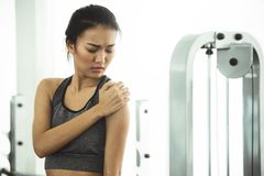 Asian woman in sportswear having shoulder pain royalty free stock photo