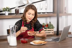 Asian woman spread strawberry jam on toast royalty free stock photography