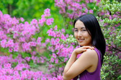 Asian woman - spring. Beautiful young Asian woman standing in front of blooming spring foliage stock photos