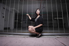 Asian woman squatting by a fence Stock Photography