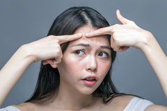Asian woman squeezing spot on forehead Stock Images