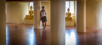 Asian woman standing between Buddhas royalty free stock photography
