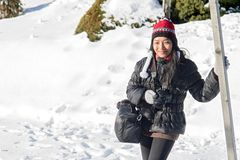 Asian woman standing with camera in a snowy nature. A beautiful woman standing with camera in a snowy nature. A happy girl in winter clothes on snow. Tourism in stock photo