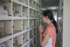 Asian woman standing at Chinese style columbarium paying praying in front of cinerary urns of ancestor stock images