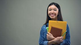 Asian woman standing with copybooks on grey background, management courses. Stock footage stock video