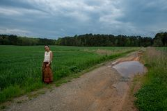 Asian woman standing on dirt road in field royalty free stock photo