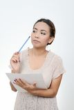 Asian woman standing holding a pencil. Royalty Free Stock Image