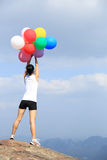 Asian woman standing on mountain peak rock with colorful balloon Royalty Free Stock Image