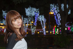 Asian woman standing in a park with lights behind her Stock Photography