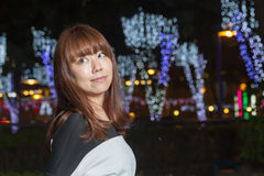 Asian woman standing in a park with lights behind her stock photo