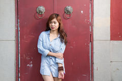 Asian woman standing by red Chinese door Royalty Free Stock Photo