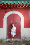 Asian woman standing by red Chinese door royalty free stock photos