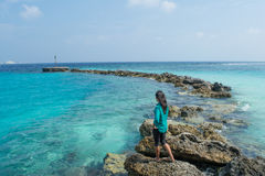 Asian woman standing on rocks at the ocean. Maldives Stock Photography