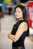 Asian Woman Standing in Supermarket Royalty Free Stock Image