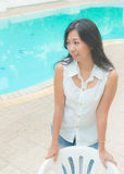 An Asian woman standing beside a swimming pool Royalty Free Stock Photos