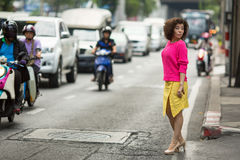 Asian woman stands near a busy city highway. Stock Images