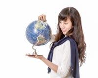 Asian woman staring at globe Stock Photography