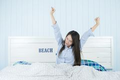 Asian woman stretching in bed after wake up in morning at bedroom after waking up in her bed fully rested. Young attractive asian woman stretching in bed after Royalty Free Stock Image