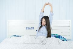 Asian woman stretching in bed after wake up in morning at bedroom after waking up in her bed fully rested. Young attractive asian woman stretching in bed after Stock Photos