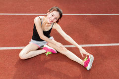 Asian woman stretching on track Royalty Free Stock Photo