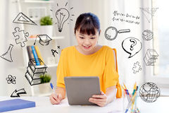 Asian woman student with tablet pc at home. People, education, high school and learning concept - happy asian young woman student in glasses with tablet pc Royalty Free Stock Images