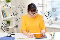 Asian woman student with tablet pc at home. People, education, high school and learning concept - happy asian young woman student in glasses with tablet pc Stock Photography