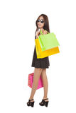 Asian woman with sunglasses turn back  hold shopping bags Royalty Free Stock Photos