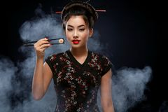 Asian woman with sushi eating sushi and rolls on a black background. Woman with sushi woman eating sushi and rolls on a light background Royalty Free Stock Image