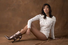 Asian woman in sweater and boots. Asian woman with winter sweater and gold boots sitting Royalty Free Stock Photo