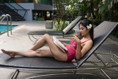 Asian woman with swimsuit read book at swimming pool. Portrait of Asian beautiful woman in red swimsuit read book and drink tomato fruit juice on chair at royalty free stock photo