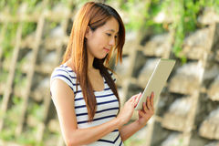 Asian woman with tablet computer outdoor Royalty Free Stock Photos