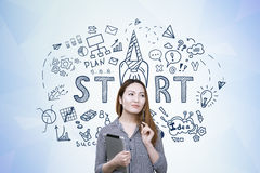 Asian woman with tablet and start up. Portrait of a young Asian woman holding a tablet computer standing near a blue wall with a start up drawing on it Stock Image