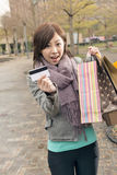 Asian woman take credit card hold shopping bags Stock Photos