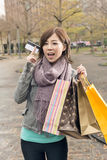 Asian woman take credit card hold shopping bags Royalty Free Stock Photo