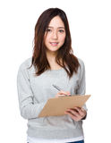 Asian woman take note on clipboard Stock Images