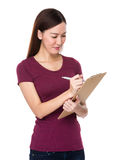 Asian woman take note on clipboard Royalty Free Stock Images