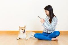 Asian woman take photo to shiba by mobile  phone Stock Photos