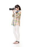 Asian woman takes pictures with photo camera Royalty Free Stock Photos