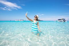 Asian Woman takes a selfie on vacation by the ocean in Thailand Royalty Free Stock Photos