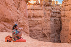 Asian woman taking a break and drinking water on trail Stock Images