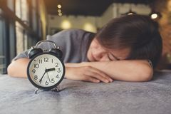 Asian woman taking a nap on the table with black alarm clock. An Asian woman taking a nap on the table with black alarm clock Stock Photography