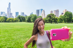 Asian woman taking phone selfie in New York city. Happy Asian woman taking smartphone selfie photo with mobile phone at sheep meadow, Central park. Girl tourist royalty free stock photography