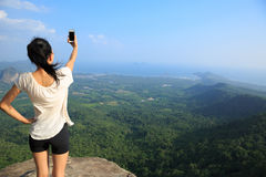 Asian woman taking photo with smart phone at mountain peak cliff Stock Photo
