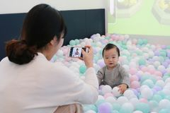 Asian woman taking pictures of her baby playing in colorful ball pool stock images