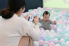 Asian woman taking pictures of her baby playing in colorful ball pool stock photography