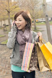 Asian woman talk on phone hold shopping bags Stock Photo