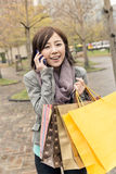 Asian woman talk on phone hold shopping bags Stock Image