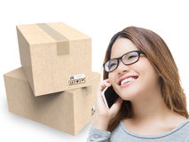 Asian woman talking on mobile phone in warehouse. With cardboard boxes stock photos