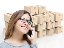 Asian woman talking on mobile phone in warehouse. With cardboard boxes stock photo